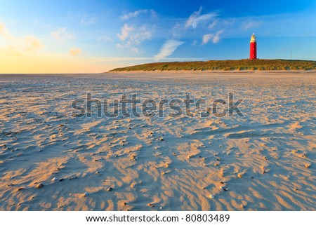 Seaside with sand dunes and lighthouse with colorfull sky at sunset