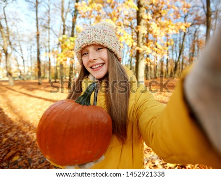 season and people concept - happy girl with pumpkin taking selfie at autumn park