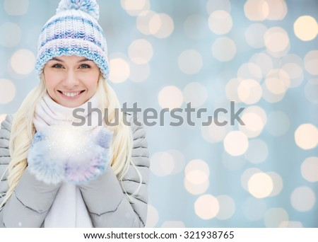 season, christmas, holidays and people concept - smiling young woman in winter clothes over lights background #321938765