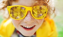 season, emotions and people concept - happy face boy, smiling boy's face close up with freckles, yellow sunglasses, mirror reflection in glasses is bokeh  yellow glowing hearts are reflected.
