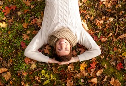 season, happiness and people concept - smiling young man lying on ground or grass and fallen leaves in autumn park