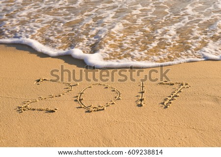 "Season of travel. Summer trips to the sea. Concept of leisure and rest. inscription ""2017"" on the wet sand of the coast #609238814"