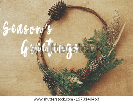 Season's greetings text sign on christmas rustic wreath flat lay. Creative rural wreath with fir branches, berries, pine cones, herbs on wooden table. Seasons greeting card