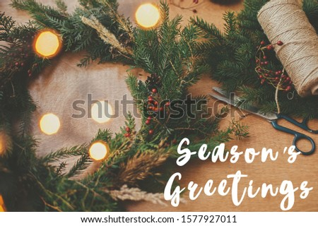 Season's greetings text sign on christmas rustic wreath flat lay. Creative rural wreath with fir branches, berries, pine cones, herbs on wooden table. Seasons greeting card #1577927011