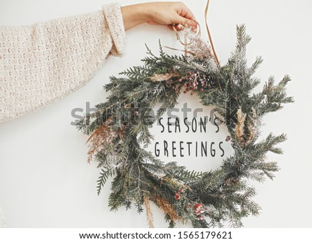 Season's greetings text sign on christmas rustic wreath in girl hand. Creative rural  wreath with fir branches, berries, pine cones, herbs hanging on white wall in room. Seasons greeting card #1565179621