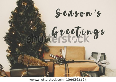 Season's greetings text sign on christmas tree in golden lights bokeh with festive stylish gifts in white room. Seasons greeting card #1566262267