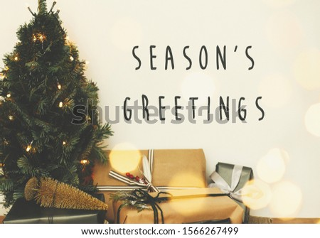 Season's greetings text sign on christmas tree in golden lights bokeh with festive stylish gifts in white room. Seasons greeting card #1566267499