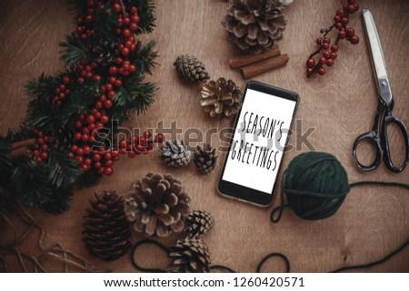 Season's greetings text sign on phone screen with rustic christmas wreath, fir branches,red berries, pine cones. Seasonal greeting card. Atmospheric image. #1260420571