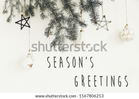 Season's greetings text sign on stylish christmas branches with glass modern ornaments hanging on white wall. Creative christmas festive decor. Seasons greeting card #1567806253