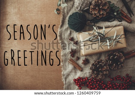 Season's greetings text sign on stylish rustic christmas gift box with fir branches, red berries, pine cones, cinnamon on rustic wood. Atmospheric image. Seasonal greeting card #1260409759