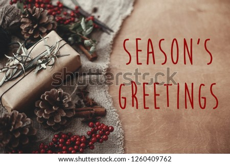Season's greetings text sign on stylish rustic christmas gift box with fir branches, red berries, pine cones, cinnamon on rustic wood. Atmospheric image. Seasonal greeting card #1260409762
