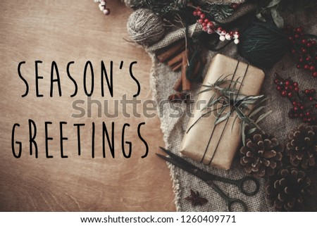 Season's greetings text sign on stylish rustic christmas gift box with fir branches, red berries, pine cones, cinnamon on rustic wood. Atmospheric image. Seasonal greeting card #1260409771
