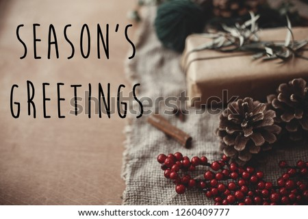 Season's greetings text sign on stylish rustic christmas gift box with fir branches, red berries, pine cones, cinnamon on rustic wood. Atmospheric image. Seasonal greeting card #1260409777