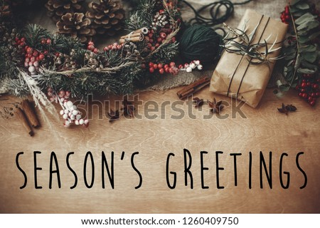 Season's greetings text sign on stylish rustic christmas wreath, gift box with fir branches, red berries, pine cones, cinnamon on rustic wood. Atmospheric image. Seasonal greeting card #1260409750