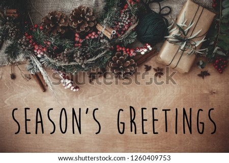 Season's greetings text sign on stylish rustic christmas wreath, gift box with fir branches, red berries, pine cones, cinnamon on rustic wood. Atmospheric image. Seasonal greeting card #1260409753