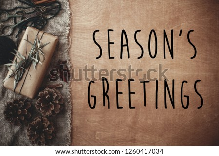 Season's greetings text sign on stylish rustic gift box with green branches, anise, pine cones, cinnamon on rustic wood. Seasonal greeting card. Simple eco present. Atmospheric image #1260417034