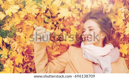 season, technology and people concept - beautiful young woman lying on ground and autumn leaves and taking selfie with smartphone