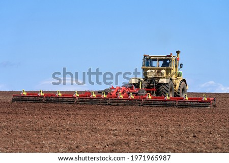 Seasonal agricultural work in the field. Heavy tractor with harrow close-up. Selective focus. Copy space.                                Photo stock ©