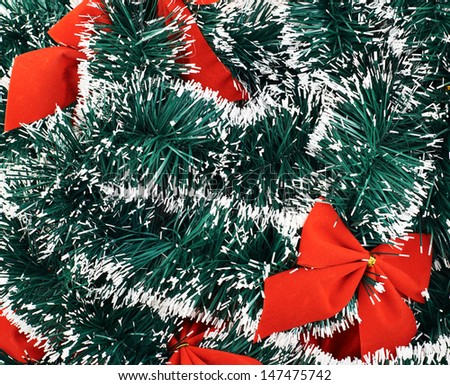 Seasonal Christmas decoration background as an xmas tree garland fragment covered with decorational red bows