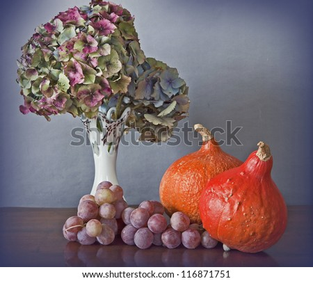 Seasonal composition, interior still life. Vase with hydrangea dry flowers, grapes and red orange pumpkins