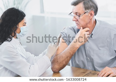 Seasonal Flu Shot. Brazilian nurse in medical mask injecting tetanus toxoid vaccine to senior retired man, copyspace