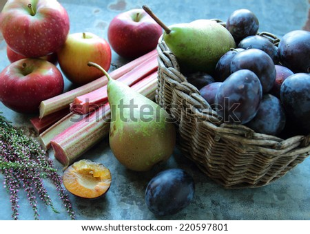 Seasonal fruits- apples, pears and plums in a wooden wicker