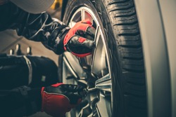 Seasonal Tires Replacement Automotive Photo Theme. Tire Sales Worker Finishing Change of Car Wheels. Closeup Photo.