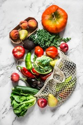 Seasonal vegetables on a marble background - kale cabbage, zucchini, eggplant, pepper, cauliflower, tomatoes, pumpkin and pears, apples, peaches. Top view