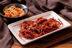 Seasoned dried shredded squid (ojingeochae muchim) with kimchi on wood table