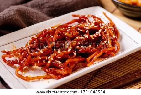 Seasoned dried shredded squid (ojingeochae muchim) with kimchi on wood table Stock photo ©