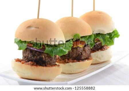 Seasoned grilled hamburger sliders on white background