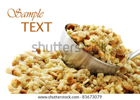 Seasoned stuffing mix spilling from stainless steel ladle on white background with copy space. Shallow dof.