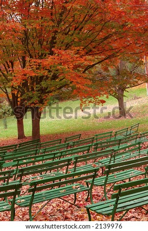 Seasongood Pavilion Benches - The green benches at Seasongood Pavilion are empty as they sit under the colorful canopy of orange foliage  in autumn. Eden Park, Cincinnati Ohio, USA