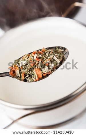 seasoning in spoon for cooking soup in pot with steam