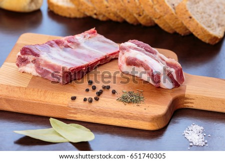 Seasoning the pork ribs with salt and different spices and hebs. Wooden cutting board over dark kitchen board #651740305