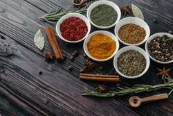 Seasonings with fresh and dried herbs in bowls on an old wooden background. Free space to copy. Indian cuisine.