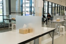 Seat for customers sitting separated in food center with table shield plastic partition to protect infection from coronavirus covid-19 in Thailand, restaurant and social distancing concept