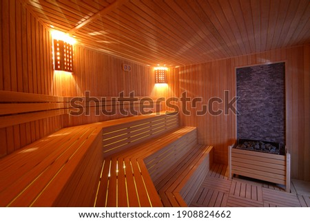 Seat in sauna room. Empty wooden steam room with stone heater.Sauna room for good health. Sauna room with traditional sauna accessories.Healthy and spa life style.