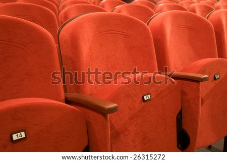 Seat number thirteen. Row of red chairs in auditorium.