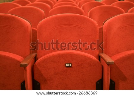 Seat number thirteen. Row of red chairs in auditorium. - stock photo