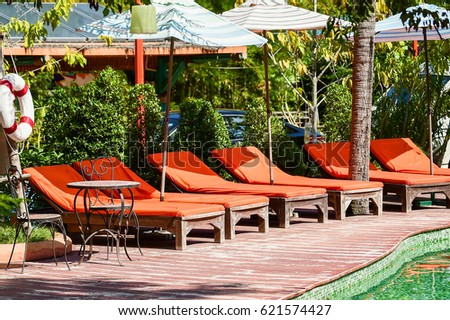 Seat Side By Pool , Relax Beach Chairs And Umbrella At Swimming Pool Side.