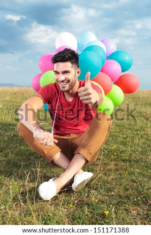 seated casual young man holding balloons outdoor and showing the thumbs up gesture while smiling for the camera - stock photo