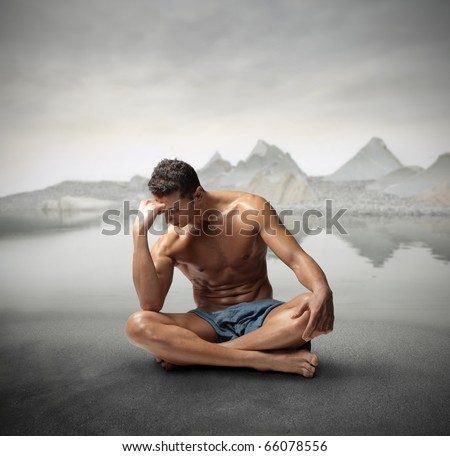 Seated handsome man reflecting with mountains on the background