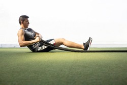 seated man doing sit-ups with rope