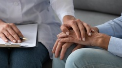 Seated on couch social service homecare nurse worker in white coat supports old patient hold hand encourages her close up, cancer diagnose, overcome illness, psychological help express empathy concept