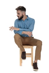 seated student looking away with hands crossed on white background