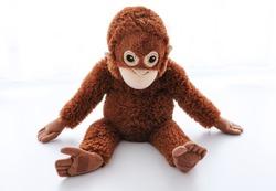 Seated toy monkey on white background
