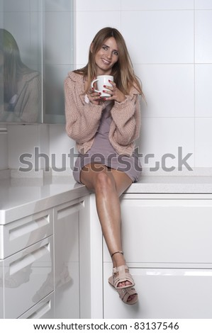 Seated woman in the kitchen with a cup - stock photo