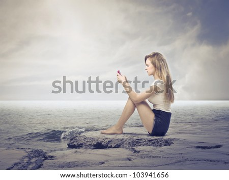 Seated young woman using a mobile phone