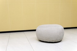 Seating area in public place is gray round fabric ottoman against backdrop of tiled walls and floors. Caring for elderly in shopping malls and government agencies.